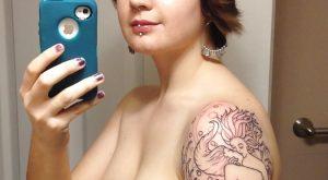 Selfie jeune brune cheveux courts piercée et tatouée sur le bras